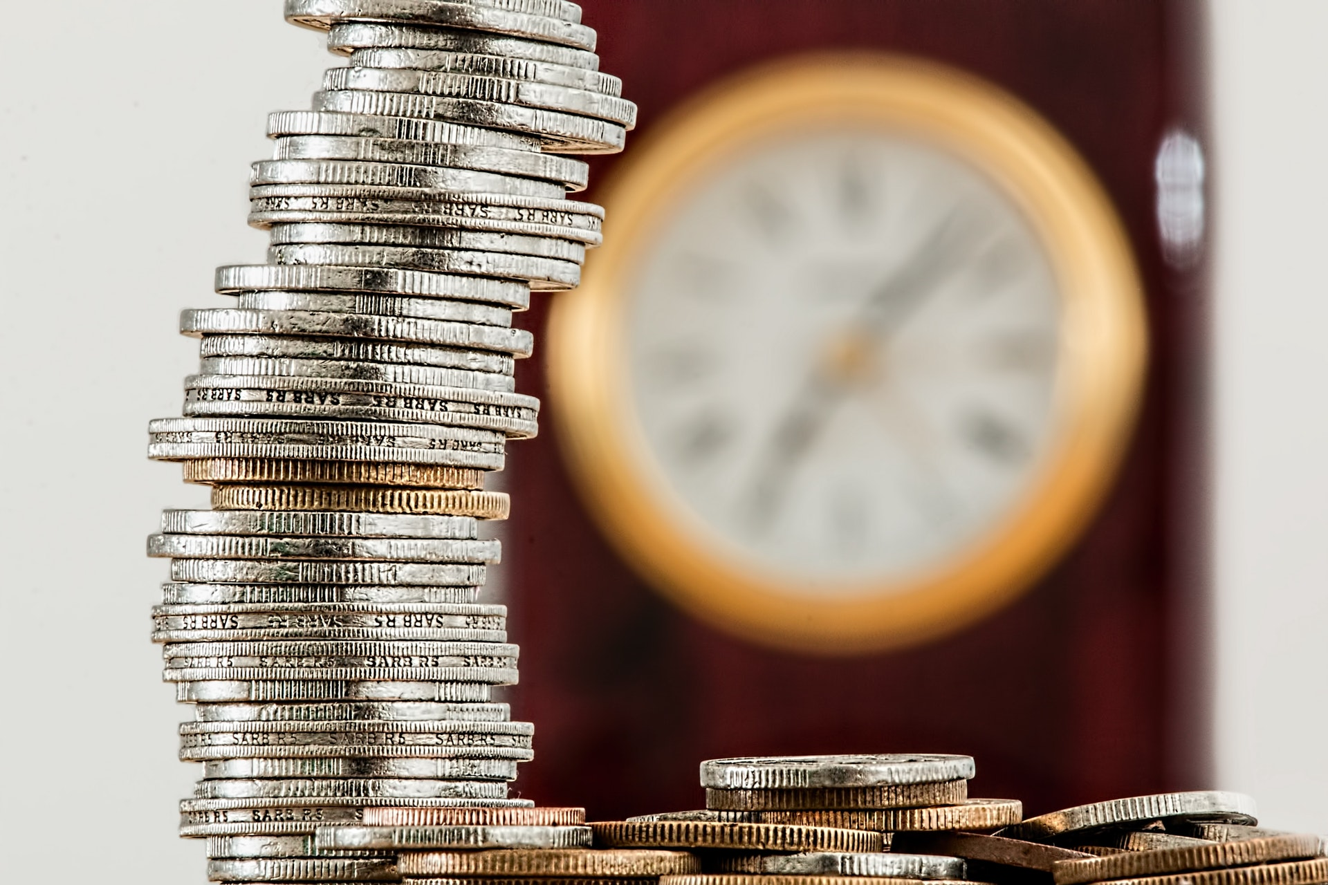 Geld op hoop met klok op achtergrond