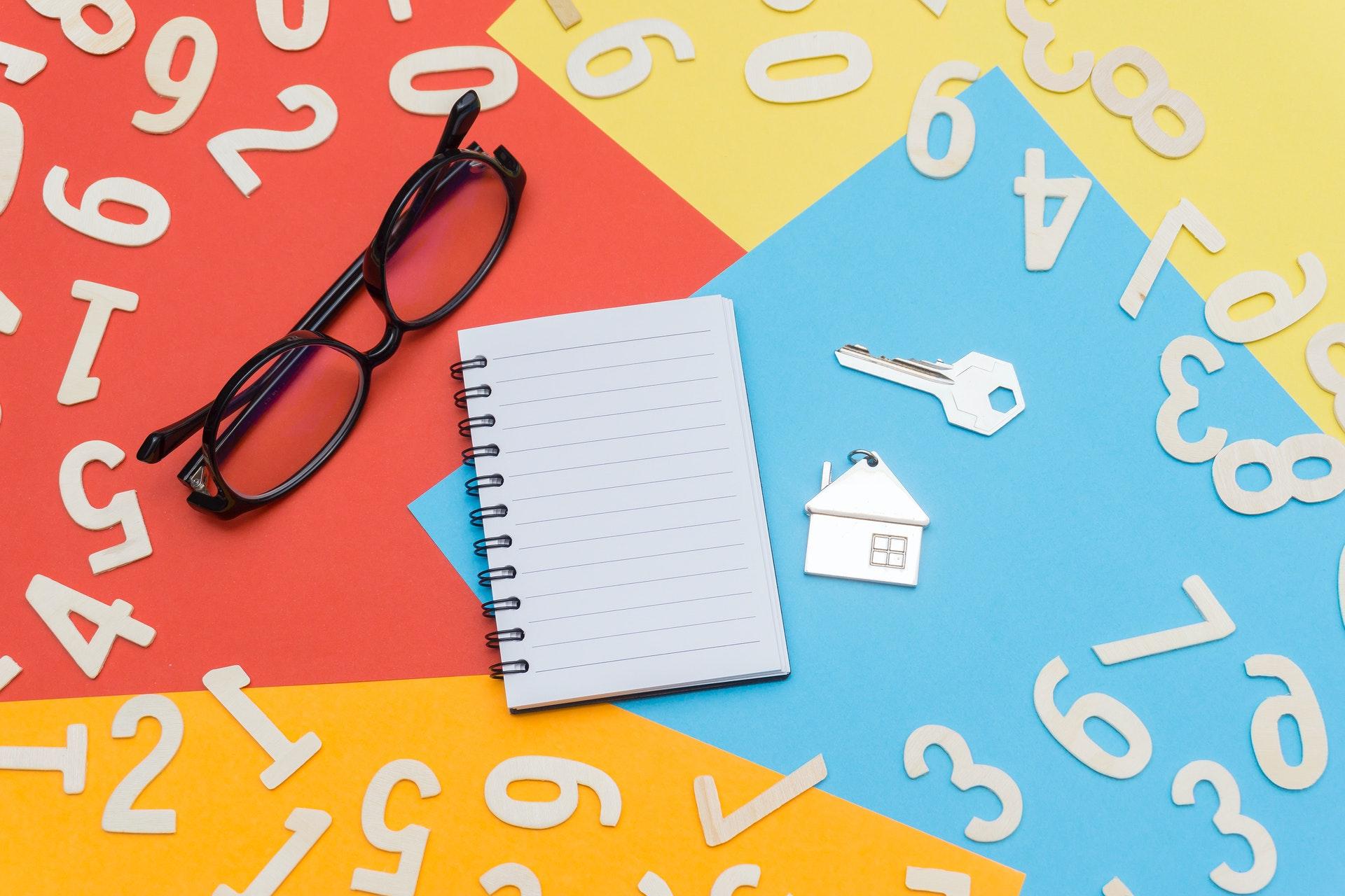 kladblok met bril, sleutel en sleutelhanger