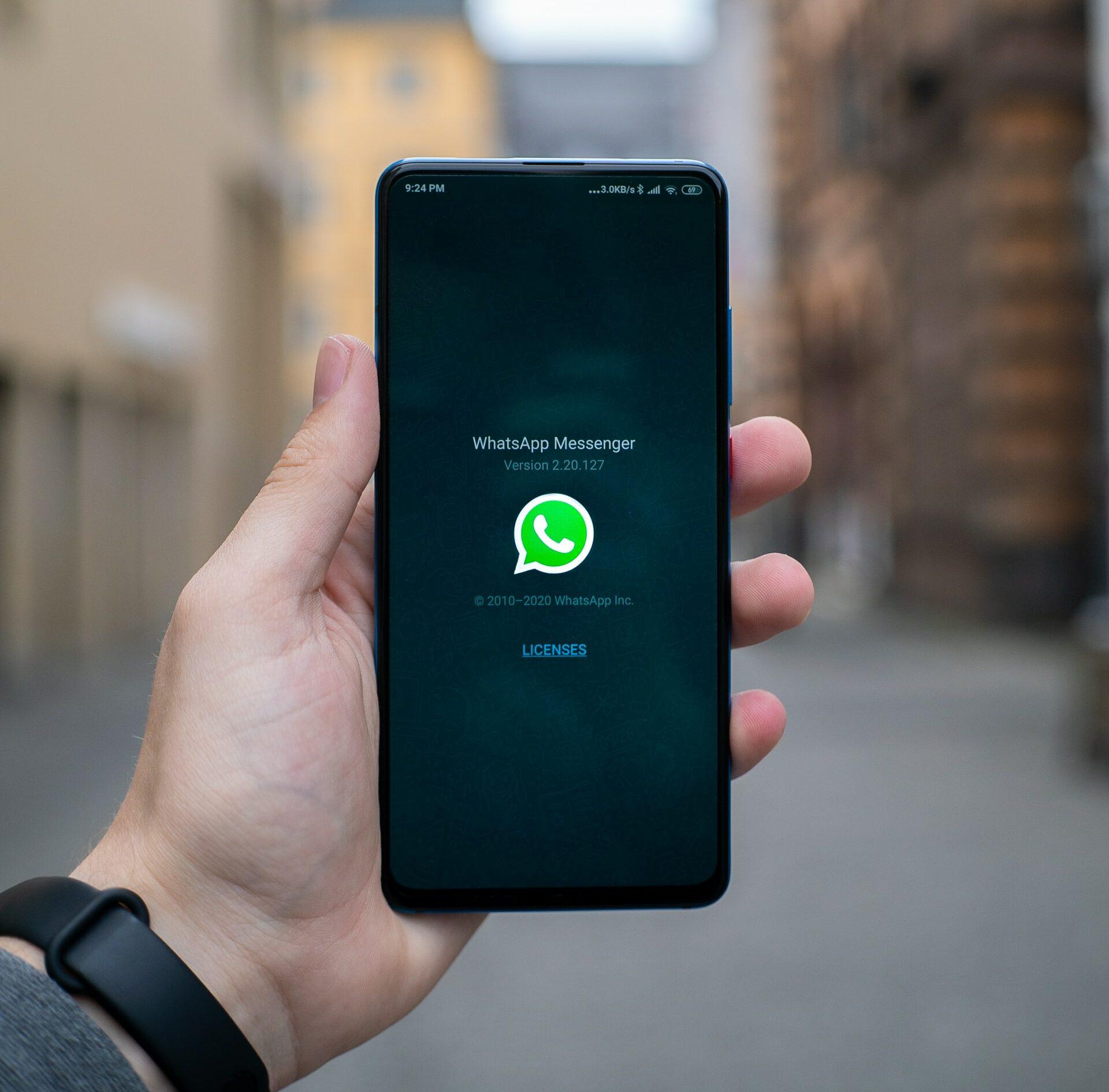 Hand houdt telefoon vast met Whatsapp