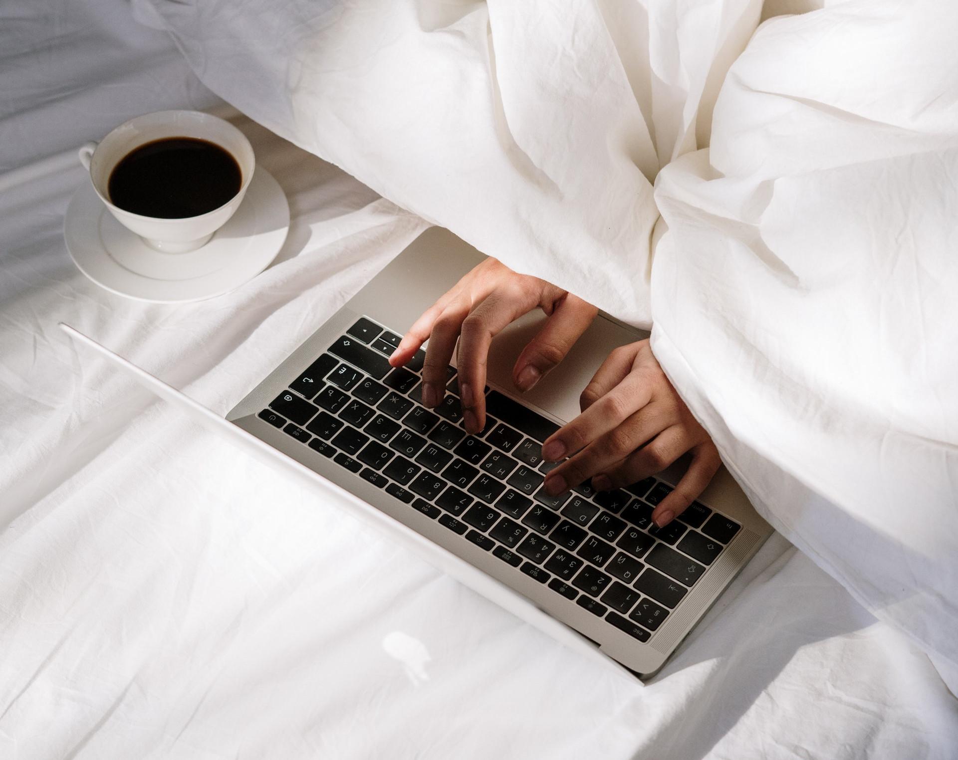 handen onder deken typen op toetsenbord