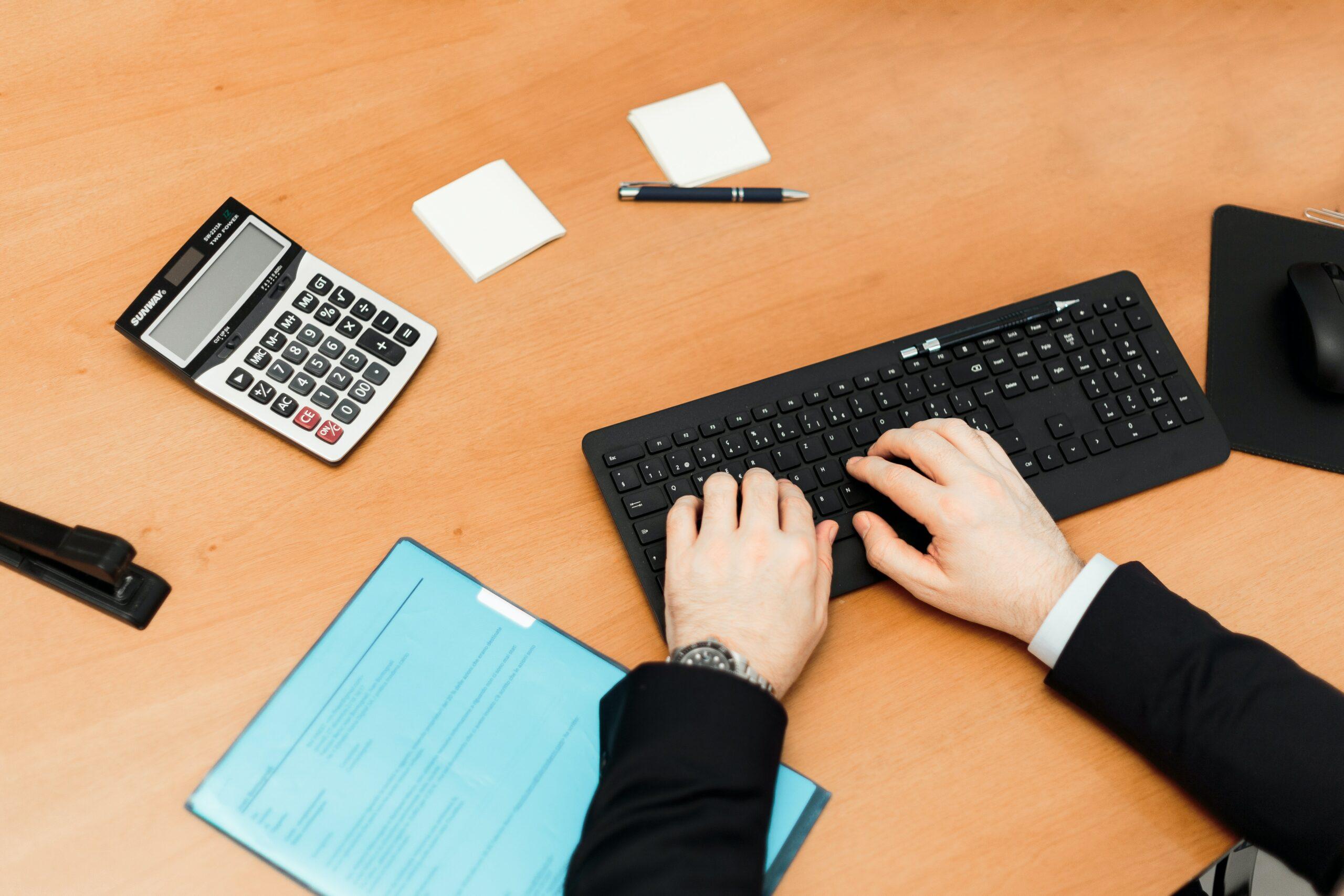 man typt op toetsenbord naast rekenmachine